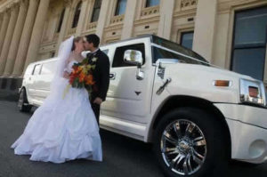 Bride and groom kissing in front of hummer limo